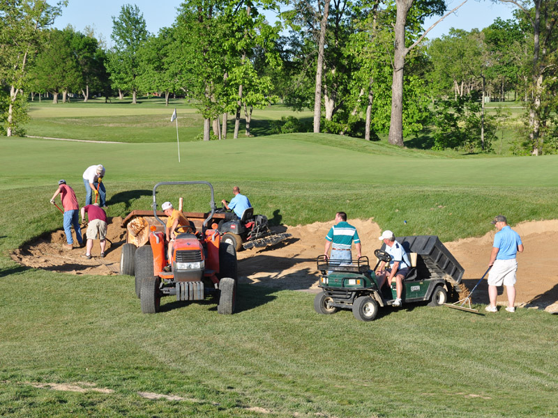 Member volunteers install sand in the new bunkers
